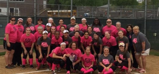 The Conant and Schaumburg softball teams posing with cancer survivor Jan Sunderlin (center), who threw out the first pitch on May 13.