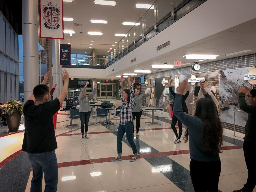 """All nine members finish the energizer by throwing their hands in the air and laughing together. After finishing the exercises, the group finishes the promotion by enjoying cheese pizza and drinks. Assistant leader Jaemie Bennett, '17, explains """"there is a place for everyone in Operation Snowball."""""""